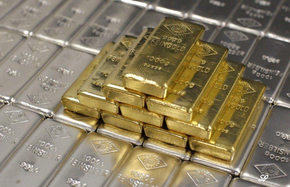 Серебряные слитки, расположенные аккуратными рядами, а на них выложенные небольшой стопкой золотые слитки