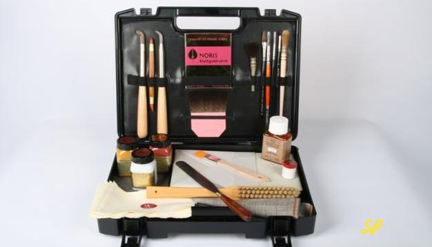 Черный раскрытый чемоданчик с разнообразными инструментами позолотчика, стеклянными флакончиками с золотой пудрой и книжкой с сусальным золотом