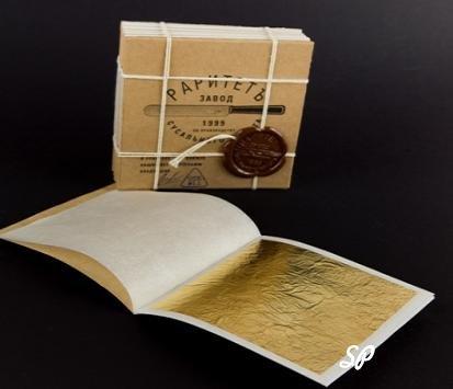 Книжка сусального золота с надписью на русском: завод раритет и сусальное золото, перевязанная веревкой и запечатанная сургучной печатью. Книжка лежит на другой, раскрытой книжке с листком сусального золота
