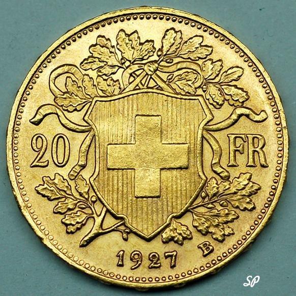 Золотой швейцарский франк достоинством в 20 франков крупным планом на сером фоне