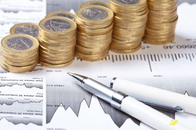 Стопки золотых монет на фоне листка с графиком