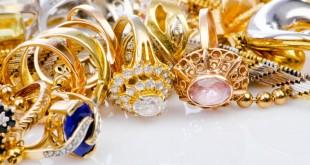 Россыпь ювелирных изделий из золота на белом фоне