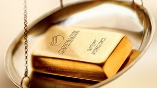 Слиток банковского золота на чаше весов